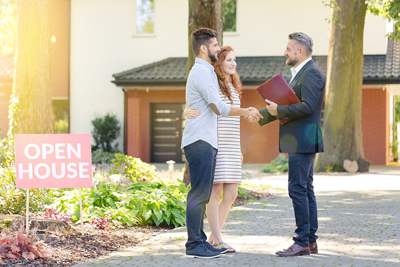 A couple shakes hands with their real estate agent.