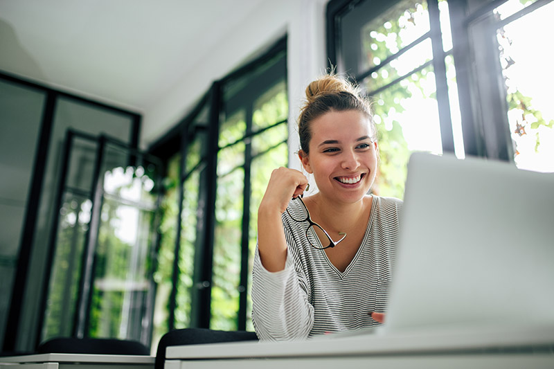 A Woman Smiling In A Bright, Modern Living Room As She Looks At Home Loan Options.