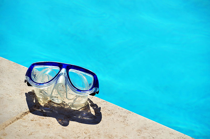A Pair Of Swimming Goggles Sit Next To A Brand New Pool On A Sunny Day.