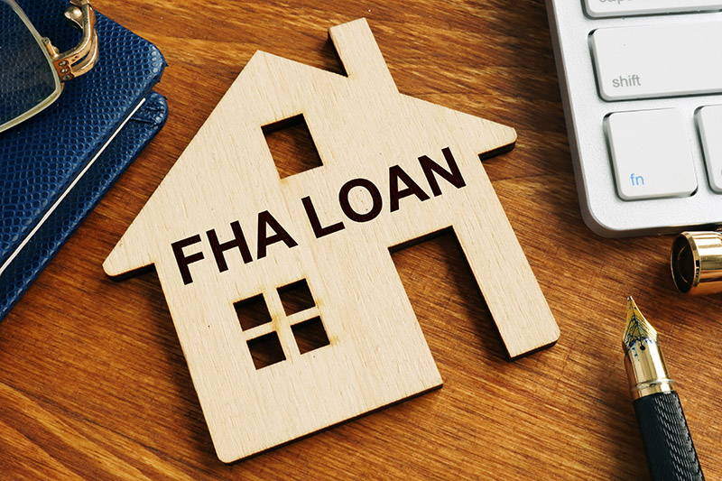 A Wooden Cutout Of A Home Representing FHA Loans.