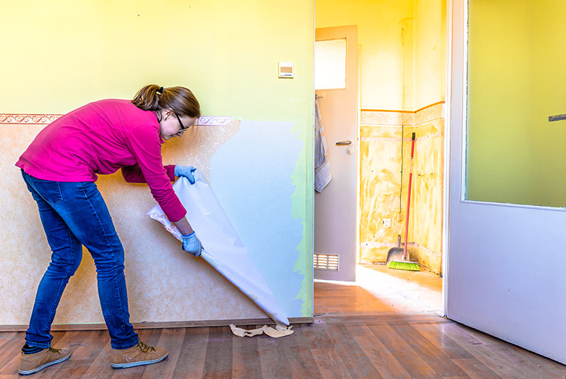 A Woman Tears Wallpaper Down In A Newly Purchased Home.
