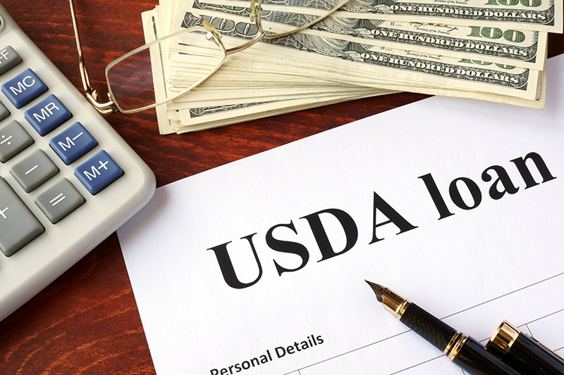 A Calculator & Stack Of Money Sits On A USDA Loan Application.