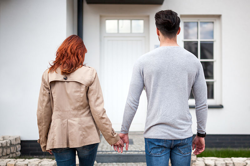 Couple Looks At Their Front Door After Closing On Their New Home.
